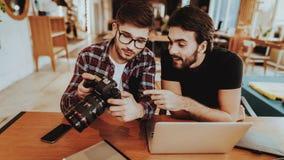 Fotografen met de Camerawerken aangaande Laptop binnen royalty-vrije stock afbeeldingen