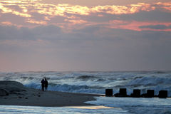 Fotografen schießen die Wellen während eines Sturms bei Sonnenaufgang lizenzfreies stockfoto