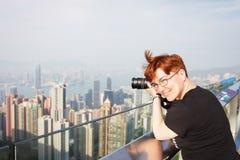 Fotografen tar fotoet av staden rödhårig kvinna som tar bilder av Hong Kong royaltyfri bild