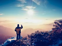 Fotografen vid den smarta telefonen tar bilden av det dimmiga bergiga landskapet Arkivfoton