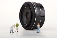 Fotografenminiaturen en Fotografische lens Stock Afbeeldingen