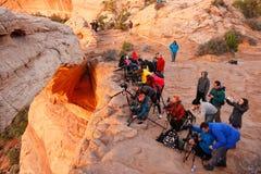 Fotografer och turister som håller ögonen på soluppgång på Mesa Arch, Canyo Royaltyfri Fotografi
