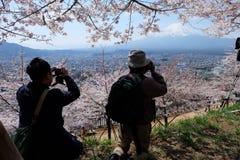 fotografer tar ett foto på den Chureito pagoden med den blåa himlen Arkivfoto