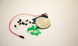 Fotografera bitcoin, arduino, transistorer och trådar Arkivbild