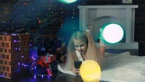 Fotograferat flickasammanträde under en julgran och lager videofilmer