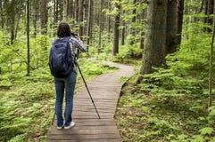 Fotograffrau mit einer Kamera und einem Stativ, die auf der EC stehen Lizenzfreie Stockfotos