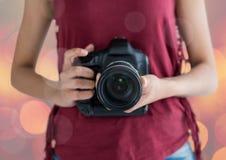Fotografhände mit Kamera Rosa und Gelb unscharfe Lichter Lizenzfreies Stockfoto