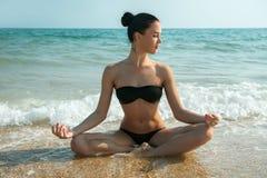 Fotografi av en härlig kvinna som kopplar av och mediterar på en bea Royaltyfri Bild