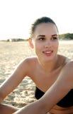 Fotografi av en härlig modell som kopplar av på en strand i vågorna Arkivfoton