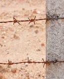 Cavo arrugginito della sbavatura che tieding su un palo del recinto Fotografia Stock