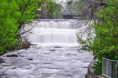 Fotografi för materiel för lång exponering för dag yttre av vattenfallet med gröna träd på Glen Falls Arkivfoto