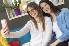 Fotografi för två vuxet le flickor med en mobiltelefon Royaltyfria Bilder