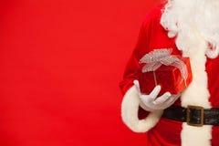 Fotografia Święty Mikołaj gloved ręki trzyma czerwonego giftbox Obrazy Stock