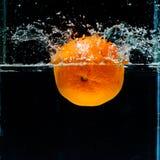 Fotografia ad alta velocità dell'arancia con spruzzata in acqua Immagine Stock