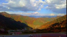 Fotografia al rallentatore, nuvole commoventi sopra la valle, strade di bobina con i lotti delle automobili stock footage