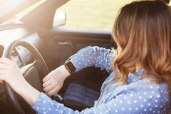 Fotografia atrakcyjna kobieta sprawdza czas na zegarku, siedzi w samochodzie, wtykającym w ruchu drogowego dżemu i być opóźniony  zdjęcia royalty free