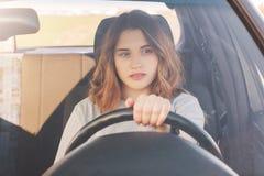Fotografia atrakcyjny żeński kierowca siedzi w samochodzie, uczy przejażdżka, być niewytrawna, rozważnego wyrażenie Kobieta w tra zdjęcie stock