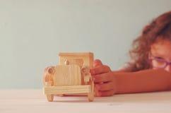 Fotografia bawić się z starym drewnianym zabawkarskim samochodem śliczny dzieciak Zdjęcie Stock
