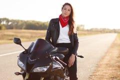Fotografia beztroski żeński rowerzysta ubierający w modnych ubraniach, pozy na ona szybki motocykl, spojrzenia przy kamerą, ciesz fotografia stock