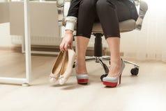 Fotografia bizneswomanu odmieniania buty pod stołem Obrazy Stock