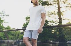 Fotografia Brodaty Mięśniowy mężczyzna Jest ubranym biel Pustą koszulkę, snapback nakrętkę i skróty w wakacje, Relaksujący czas b fotografia stock