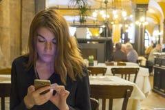 Fotografia brunetki damy czytelnicza wiadomość na telefonie komórkowym, ubierająca w czarnej bluzce, siedzi w kawiarni obraz royalty free