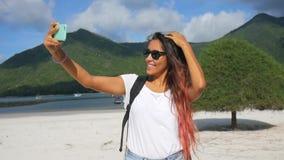 Fotografia caucasiano asiática nova do autorretrato da mulher da raça misturada com o telefone esperto da pilha móvel na praia de filme
