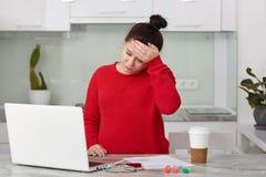 Fotografia ciężarna Kaukaska kobieta migrenę, utrzymań czoło ręka, jest ubranym przypadkowego czerwonego pulower, pracuje na lapt zdjęcie stock
