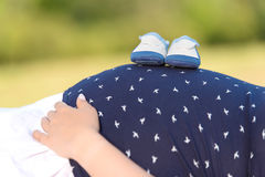 Fotografia ciężarny brzuch z dziecko butami Fotografia Stock