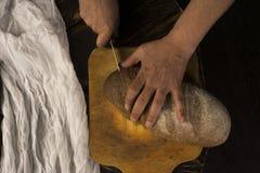 A fotografia conceptual da arte de uma mulher adulta entrega o pão do corte com a Fotografia de Stock