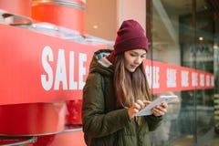 Fotografia conceptual A menina escolhe produtos em linha na venda imagens de stock