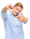 Fotografia de quadro feliz do homem novo usando os dedos isolados no whi Foto de Stock Royalty Free