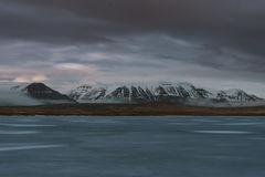 Fotografia del paesaggio di stordimento Islanda accampandosi in un lago congelato Le nuvole lunatiche stanno capitando mentre il  Fotografia Stock