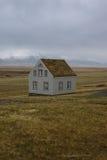 Fotografia del paesaggio di stordimento Islanda Casa sola nei campi con le montagne nevose nei precedenti Immagine Stock