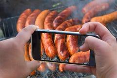 Fotografia delle salsiccie al forno, carne dell'alimento Foto di carne al forno, kebab con lo smartphone Le mani che prendono la  fotografia stock
