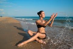 Fotografia di bello modello che si rilassa su una spiaggia nelle onde Fotografie Stock