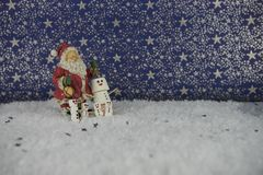 Fotografia do alimento do Natal dos marshmallows dados forma como o boneco de neve na neve com teste padrão de estrelas no fundo  Imagens de Stock