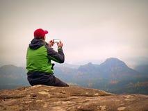 Fotografia do homem pelo telefone Viagem nas montanhas, império afiado da rocha fotos de stock