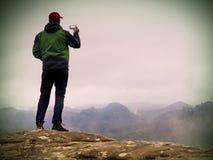 Fotografia do homem pelo telefone Viagem nas montanhas, império afiado da rocha imagem de stock royalty free