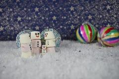 Fotografia do inverno do Natal dos marshmallows dados forma como o boneco de neve na neve com teste padrão de estrelas no fundo c Foto de Stock Royalty Free