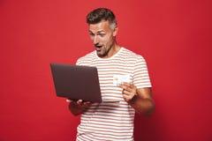 Fotografia dorosły mężczyzna ono uśmiecha się w pasiastej koszulce podczas gdy trzymający cred zdjęcie stock
