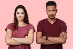 Fotografia dwa obrażającego młodzi ludzie w miłości, utrzymanie ręki krzyżować, kryzys w ich rodzinie, poza przy różową studio śc fotografia stock