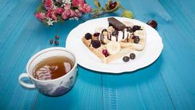 Fotografia dwa Wiedeńskiego opłatka, nalewająca z czekoladą z jagodami i lody na drewnianym stole na deskach kasztany, herbata, Zdjęcia Royalty Free