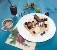 Fotografia dwa Wiedeńskiego opłatka, nalewająca z czekoladą z jagodami i lody na drewnianym stole na deskach kasztany, herbata, Obrazy Royalty Free
