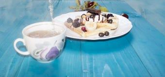 Fotografia dwa Wiedeńskiego opłatka, nalewająca z czekoladą z jagodami i lody na drewnianym stole na deskach kasztany, herbata, zdjęcie royalty free