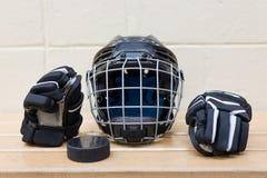 Fotografia dzieciaka ` s hokejowy wyposażenie: łuny, hełm i krążek hokojowy, Przekładnia jest na ławce Obrazy Royalty Free