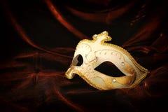 Fotografia elegancki i delikatny złoto, biała venetian maska nad ciemnym aksamita i jedwabiu tłem obraz royalty free