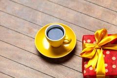 Fotografia filiżanka kawy i śliczny zawijający prezent na cudownym br Obrazy Royalty Free