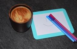 Fotografia filiżanka kawy na tle magnesowa deska i porad pióra Naszły kawowy kolor z powiewną pianą i b obraz royalty free