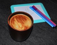 Fotografia filiżanka kawy na tle magnesowa deska i porad pióra Naszły kawowy kolor z powiewną pianą i b fotografia royalty free
